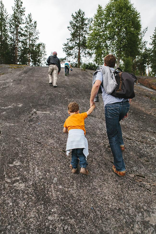 Illustrasjonsfoto av to voksne og to barn som går opp en bratt bakke i skogen på sommerstid.