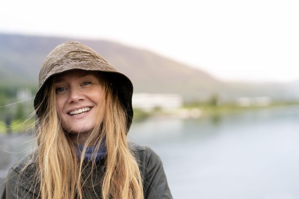 Nærbilde av ung dame som smiler i lett regnvær, med hette trukket over hode.